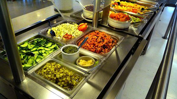 Kouluruokailu. Pöytä, jossa tarjolla erilaisia salaatteja ja lämmintä ruokaa.