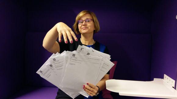 Naisen toisessa kädessä on paljon papereita. Hän aikooo ottaa niistä yhden toisella kädellä.