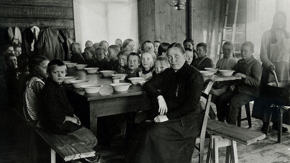Opettaja ja koululaisia istuu pöytien ääressä lautaset edessään kouluruokailussa.