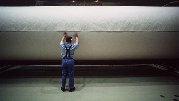 Mies seisoo ison paperirullan edessä paperitehtaalla.