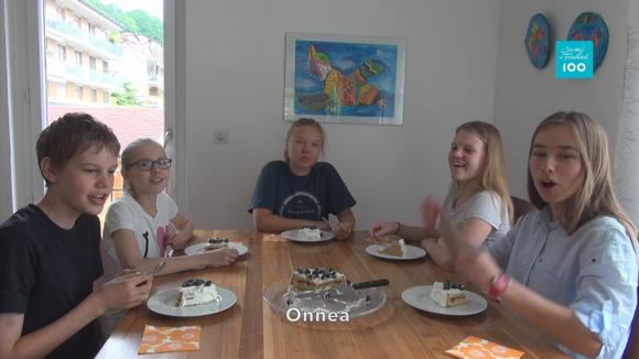 Poika ja neljä tyttöä istuvat pöydän ympärillä edessään kakkulautaset.