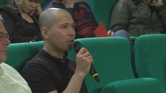 Mies puhuu mikrofoniin.