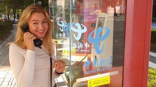 Kuvassa tyttö puhuu kiinalaisessa puhelinkopissa puhelimeen.