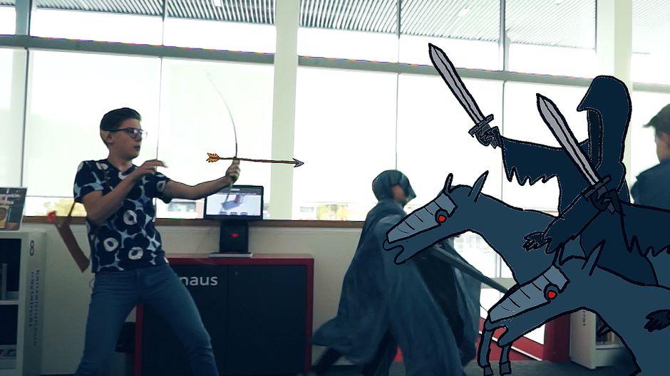 Video: Kuvassa nuori mies ampuu jousipyssyllä piirrettyjä miekkamiehiä.