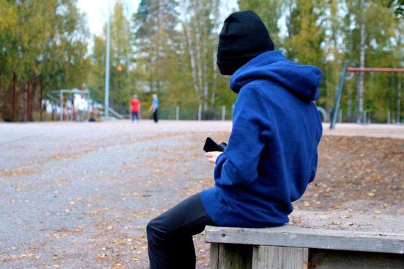 Nuori katsoo kännykkää koulun pihalla.