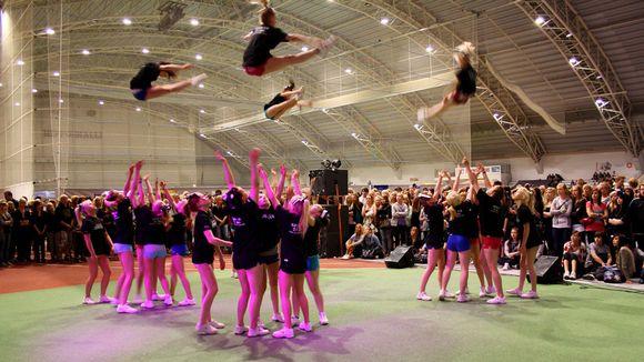 Cheerleading esitys urheiluhallissa.