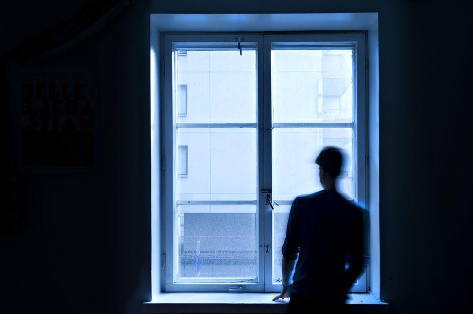 Nuori katsoo ikkunasta.