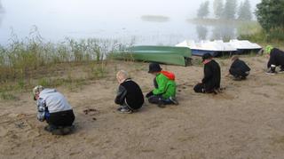 Lapsia syksyisellä hiekkarannalla.