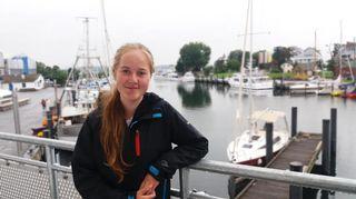 Kuvassa lukiolainen tyttö veneiden edessä.