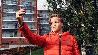Poika ottaa kuvaa itsestään älypuhelimella.