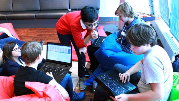 Kuvassa nuoret ovat kannettavien tietokoneiden äärellä säkkituoleissa.