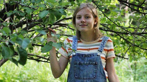 Kuvassa tyttö puiden oksien keskellä.