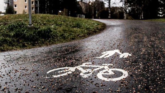 Syksyinen maisema pyörätiestä, jossa jalankulkija ja pyöräilijä merkit.