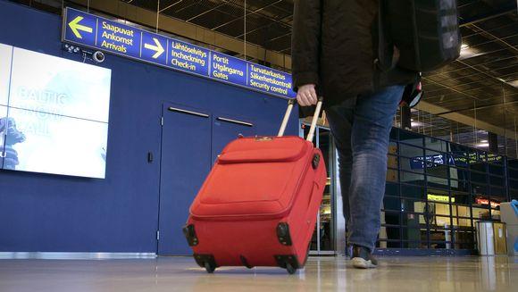 Matkustaja vetää perässään matkalaukkua lentokentällä.