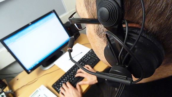 Mies istuu tietokoneen äärellä headset-luurit päässään