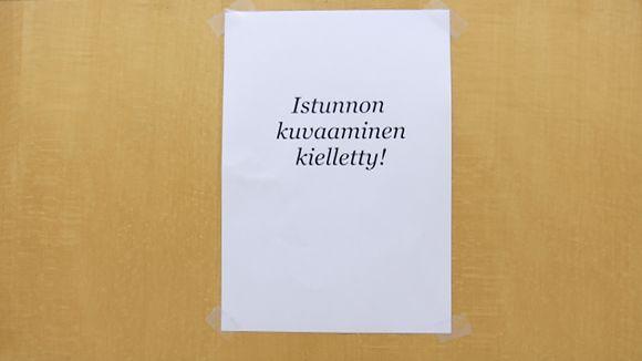 Kyltti istunnon kuvaamiskiellosta Oulun käräjäoikeuden istuntosalin ovessa 12.10.2016
