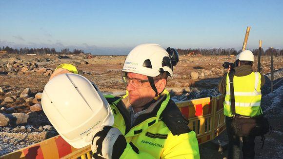 Rakentamisjohtaja Jouni Sipiläinen esitteli Hanhikivi 1 -ydinreaktorin sijaintipaikkaa 2016 auringonpaisteessa ja kypärä päässä.