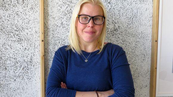 Opettaja Minna Timonen seisoo seinän edessä.