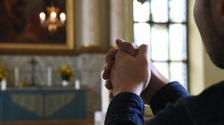 Mies rukoilee kirkon alttarin edessä.