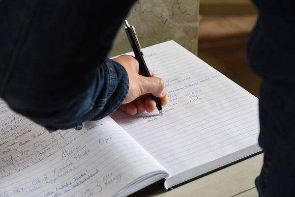 Mies kirjoittaa nimeään Oulun tuomiokirkon vieraskirjaan.