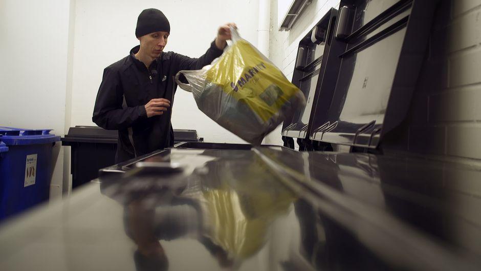 Onni Tonkija lajittelee jätteitä samalla kun hän dyykkaa jätehuoneessa.