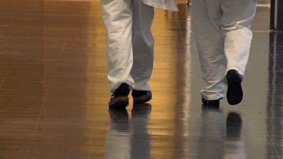 Kaksi valkohousuista henkilöä kävelee sairaalan käytävällä .
