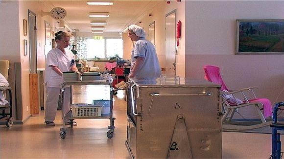 Henkilökuntaa vanhainkodissa kuljettamassa ruokakärryä ja astioita.