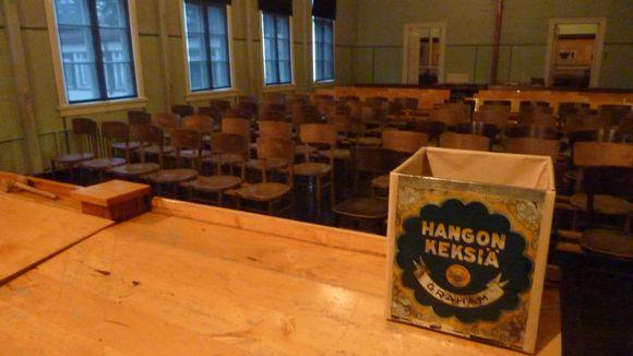 eduskuntamuseon istuntosali ja pöydällä vaaliuurna eli hangon keksi -laatikko