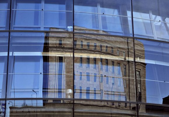 Eduskuntatalon heijastus eduskunnan Pikkuparlamentin ikkunoissa.