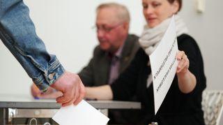 Henkilö laittaa äänestyslippua uurnaan.