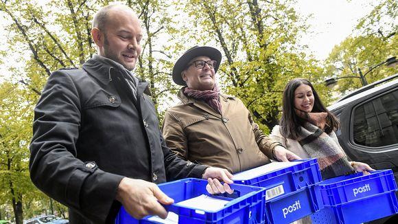 kolme kansanedustajaa kantaa laatikoissa kannattajakortteja