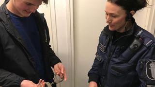 Niko Sengström tutkii poliisin käsirautoja.