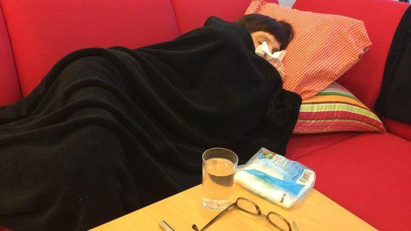 Nainen makaa punaisella sohvalla mustan peiton alla nenäliina kasvoilla.
