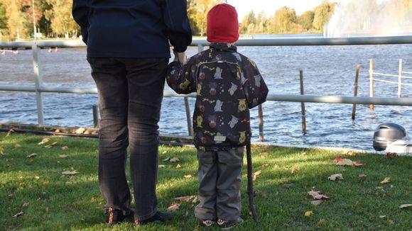 Lapsi ja aikuinen katsovat joelle.
