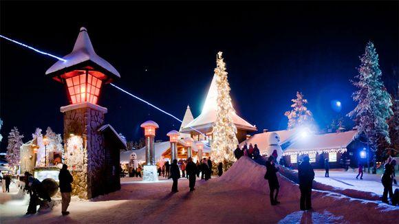Turistit iltatunnelmassa Joulupukin pajakylässä Rovaniemen Napapiirillä