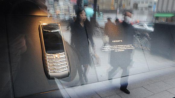 Kadulla kävelevät ihmiset heijastuvat näyteikkunasta.