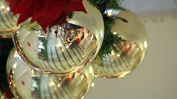 Jouluisia koristepalloja, joista heijastuu kauppakeskuksen käytävä