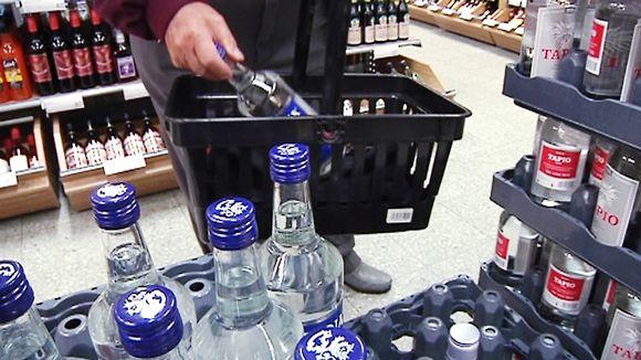 Asiakas siirtää viinapulloa ostoskoriin Alkossa.