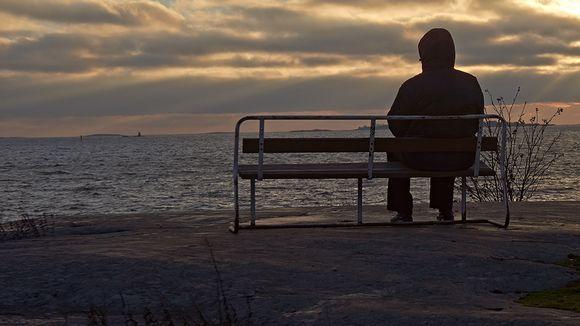 Henkilö istuu puiston penkillä pimenevässä illassa ja tuijottaa merelle.