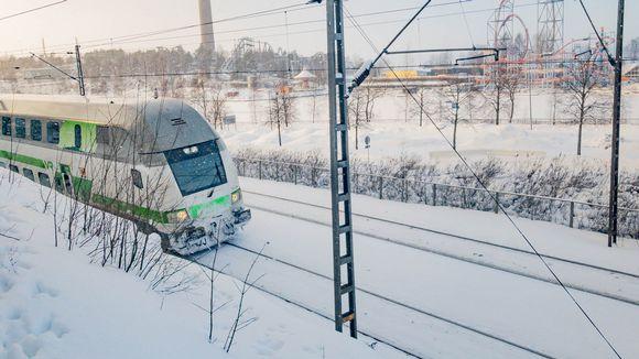 Juna ajaa lumisella radalla Tampereen Näsinkallion kupeessa