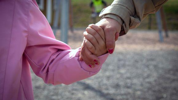 Lapsi ja äiti pitävät toisiaan kädestä