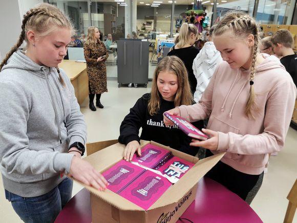 Koululaiset avaavat pahvilaatikkoa, jossa on lahjoituskirjoja.