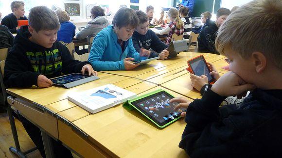 Lapsia pulpettien ääressä iPadien kanssa