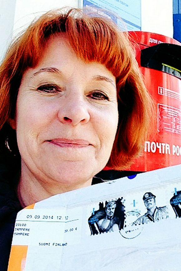 Marja Manninen pitää käsissään postipakettia