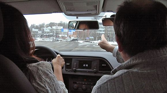 Ajo-opettaja neuvoo oppilasta autossa.