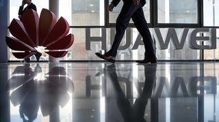 Mies kävelee Huawei logon ohi