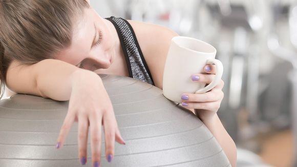 Väsynyt nainen kahvikuppi kädessä jumppapalloon nojaten.