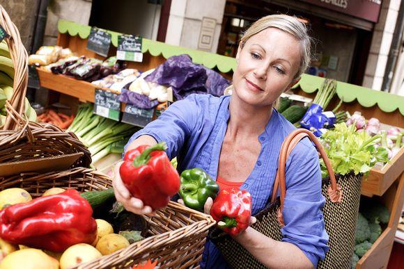 Naine vihannestiskillä ostoksilla