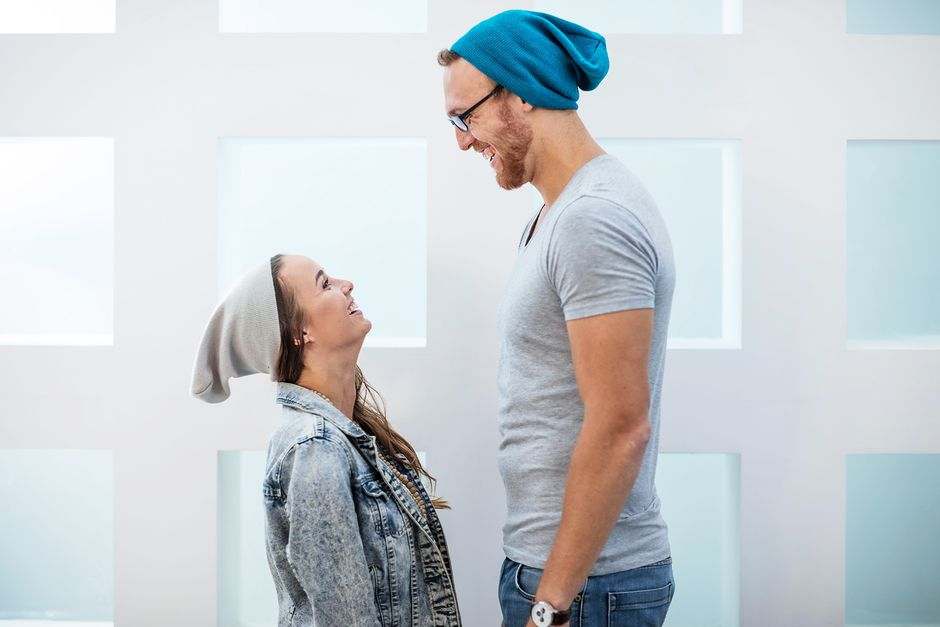 Pitkä mies ja lyhyt nainen nauravat toisilleen.