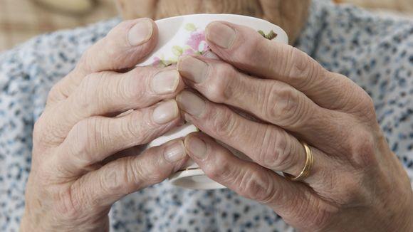 Vanhempi nainen juo kahvia.